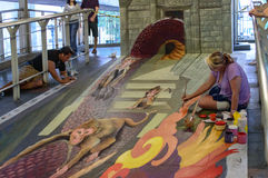 Un artista (Julie Kirk Purcell) durante il disegno e la pittura la sua illustrazione 3D. Immagine Stock