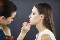 Un artiste de maquillage s'applique le maquillage à une jeune fille photo stock
