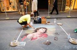 Un artiste de rue dessine l'image sur l'asphalte photo stock