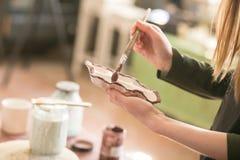 Un artiste féminin de l'atelier peint un plat céramique photographie stock libre de droits