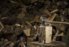 Un'ascia che attacca in un bello pezzo di legna da ardere Fotografie Stock