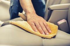 Un asiento de carro del cuero de la limpieza del hombre con el paño de la microfibra Foto de archivo libre de regalías