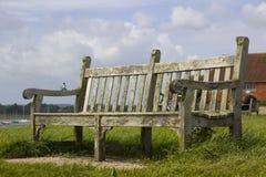 Un asiento público resistido necesitando el mantenimiento que pasa por alto el puerto en el pueblo de Bosham en Sussex del oeste Fotografía de archivo libre de regalías