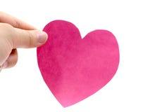 Un asimiento de la mano un corazón rosado Imagenes de archivo