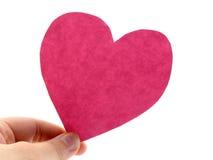 Un asimiento de la mano un corazón rosado Imagen de archivo libre de regalías