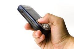 Un asimiento de la mano un microteléfono Imagen de archivo libre de regalías