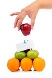 Un asimiento de la mano una manzana en la pirámide de la fruta Imagen de archivo