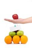Un asimiento de la mano una manzana en la pirámide de la fruta Imágenes de archivo libres de regalías