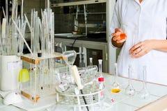 Un assistant de laboratoire féminin, un docteur, un chimiste, travaux avec des flacons, tubes à essai, fait des solutions, médeci image libre de droits