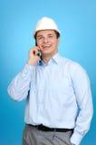 Un assistente tecnico con il cappello duro blu che comunica sul mobile Fotografie Stock Libere da Diritti