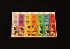 Un assortiment de pilules dans une boîte hebdomadaire colorée de pilule sur un fond noir photographie stock