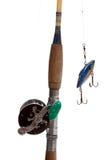 Un asta, una bobina e un richiamo di pesca su una priorità bassa bianca Immagini Stock Libere da Diritti