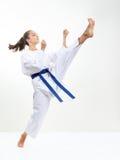 Un athlète avec des battements bleus d'une ceinture donnent un coup de pied la jambe Images libres de droits