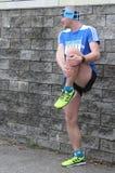 Un athlète faisant l'étirage avant un début d'une concurrence courante image stock