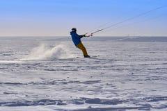 Un athlète masculin s'est engagé dans la neige kiting sur la glace d'un grand lac neigeux Il va skier dans la neige Photos libres de droits