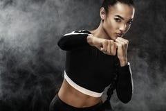 Un atlético fuerte, boxeador de la mujer, encajonando en el entrenamiento en el fondo negro Concepto del boxeo del deporte con el Foto de archivo libre de regalías