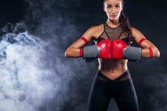 Un atlético fuerte, boxeador de la mujer, encajonando en el entrenamiento en el fondo negro Concepto del boxeo del deporte con el Fotografía de archivo libre de regalías