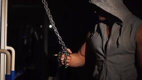 Un atleta bombea sus músculos del brazo con una cadena en el gimnasio en un fondo oscuro, almacen de metraje de vídeo