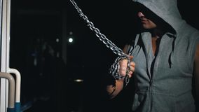 Un atleta bombea sus músculos del brazo con una cadena en el gimnasio en un fondo oscuro, metrajes