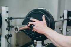 Un atleta con las manos grandes a?ade el peso por los discos del metal al aparato de entrenamiento en el centro de formaci?n equi fotografía de archivo