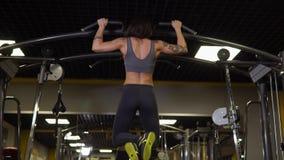 Un atleta joven en buena forma física hace tirón-UPS en el club de fitness metrajes