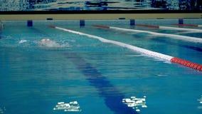 Un atleta joven nada rápidamente en el entrenamiento en la cámara lenta metrajes