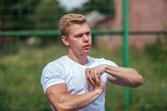 Un atleta maschio va dentro per gli sport all'aperto Armi muscolari Blonde in una maglietta bianca Stile di vita del Immagine Stock