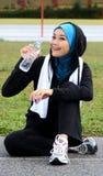 Un atleta musulmano grazioso della donna che riposa mentre bevanda Fotografia Stock Libera da Diritti