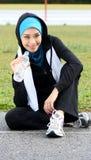Un atleta musulmano grazioso della donna che riposa mentre bevanda Fotografia Stock