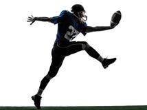 Siluetta di segnatura di atterraggio dell'uomo del giocatore di football americano fotografie stock