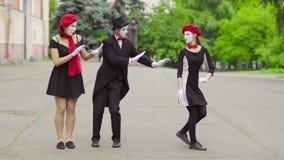 Un atto divertente di tre mimi nella via della città video d archivio