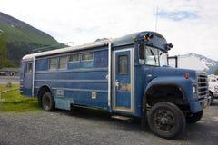 Un autobús escolar viejo convertido en un motorhome parqueado por el mar en Alaska fotografía de archivo