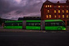 Un autobús moderno verde se está moviendo en la ciudad por la tarde imagenes de archivo