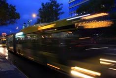 Un autobus brouillé sur l'avenue au crépuscule Image libre de droits