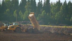Un autocarro con cassone ribaltabile di estrazione mineraria scarica il suolo e la sabbia stock footage