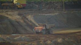 Un autocarro con cassone ribaltabile vuoto di estrazione mineraria guida lungo il pendio della collina archivi video