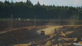Un autocarro con cassone ribaltabile vuoto di estrazione mineraria guida lungo il pendio della collina video d archivio