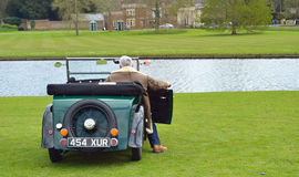 Un'automobile d'annata di Morris Minor ha parcheggiato vicino all'acqua con l'autista Fotografia Stock Libera da Diritti