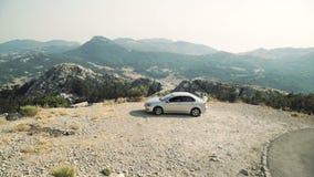 Un'automobile d'argento guida lungo una strada della montagna nei precedenti di un paesaggio della montagna archivi video