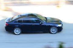 Un'automobile dei blu navy che passa tramite la strada Fotografia Stock