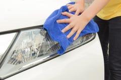 Un'automobile di pulizia della donna con il panno del microfiber Fotografia Stock