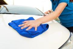 Un'automobile di pulizia della donna con il panno del microfiber Immagine Stock