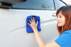 Un'automobile di pulizia della donna con il panno del microfiber Immagine Stock Libera da Diritti