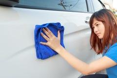 Un'automobile di pulizia della donna con il panno del microfiber Immagini Stock Libere da Diritti