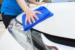 Un'automobile di pulizia della donna con il panno del microfiber, concetto dettagliante dell'automobile Fotografia Stock