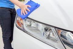 Un'automobile di pulizia della donna con il panno del microfiber, dettagliare dell'automobile Immagini Stock