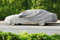 Un'automobile parcheggiata con rivestimento protettivo in tempo del sole immagini stock