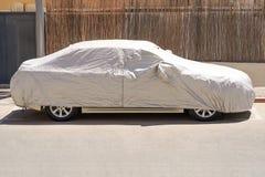 Un'automobile parcheggiata con rivestimento protettivo in tempo del sole fotografia stock libera da diritti
