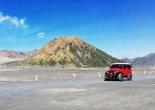 Un'automobile rossa in montagna di Bromo fotografia stock