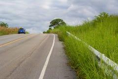 Un'automobile sulla strada rurale avanti alla montagna Fotografie Stock Libere da Diritti